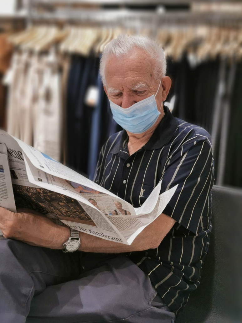Man Wearing a Mask and Reading a Newspaper
